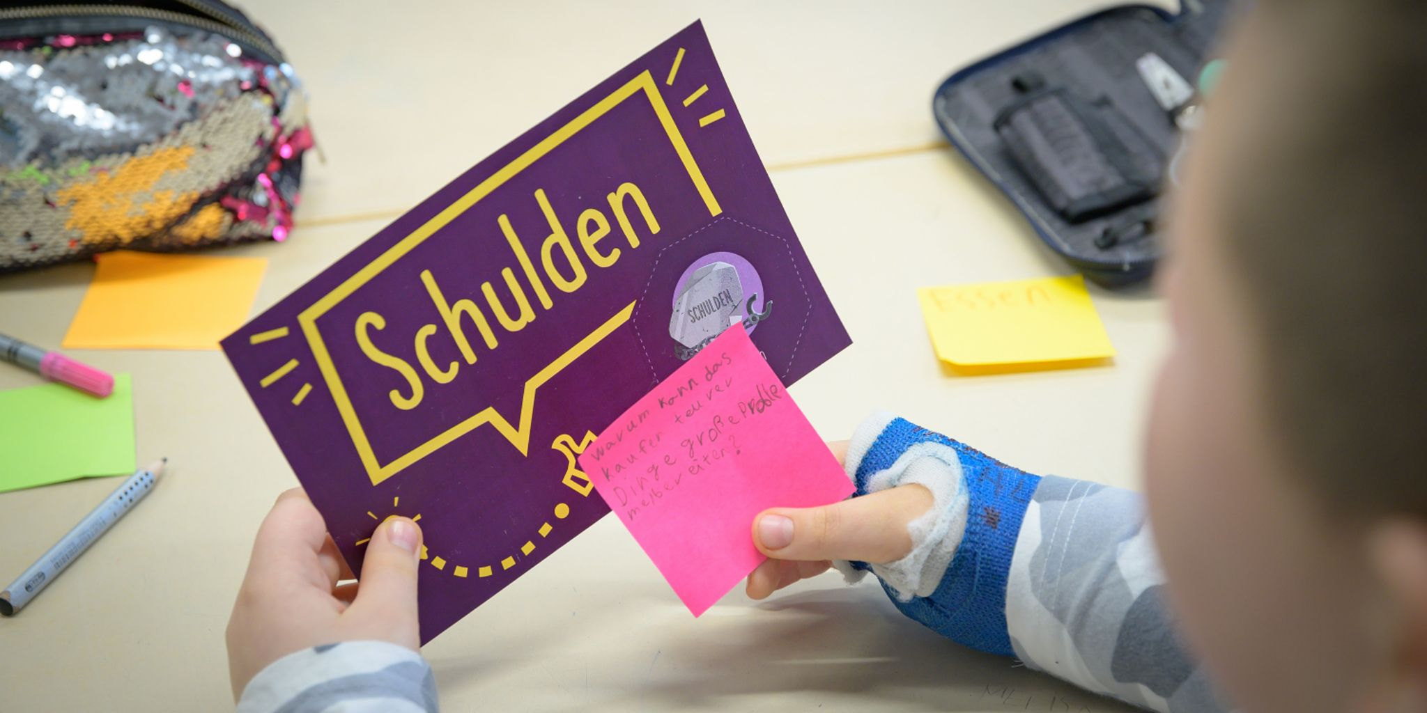 Financial education for children: Child looks at a flash card on the topic of debt.